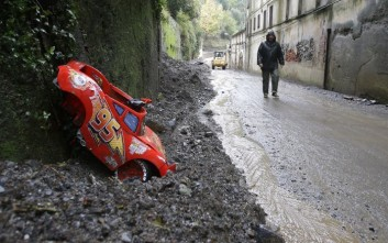 A man walks on a muddy road as heavy rains have been battering northern Italy for the last few days, in Voltri, near Genoa, Italy, Monday, Nov. 17, 2014. (AP Photo/Antonio Calanni)