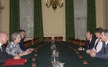 Britain's Prime Minister Theresa May, second left, sits with First Secretary of State Damian Green, left, and Government Chief Whip Gavin Williamson during their meeting with the Democratic Unionist Party (DUP) leader Arlene Foster, second right, DUP Deputy Leader Nigel Dodds, and DUP MP Jeffrey Donaldson, right, inside 10 Downing Street in central London, Monday June 26, 2017. Arlene Foster says that she struck a deal with Theresa May's Conservatives to support her minority government. (Daniel Leal-Olivas/Pool via AP)