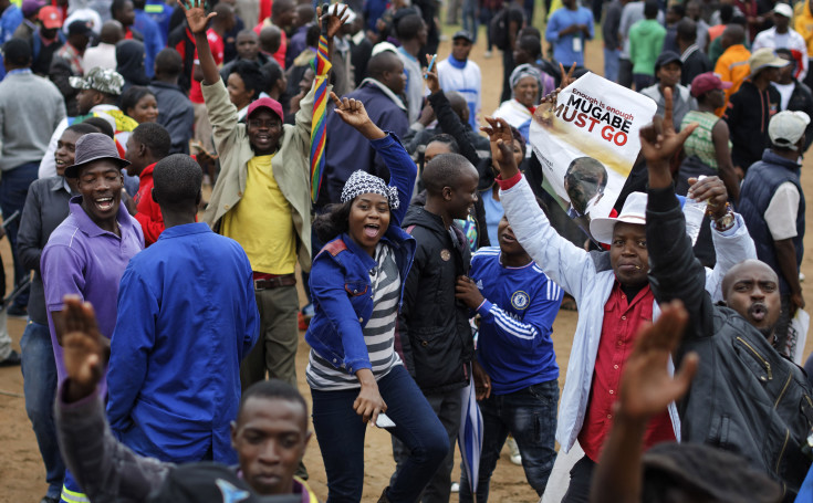 Protesters dance and sing, one holding a poster asking President Mugabe to step down, at a demonstration at Zimbabwe Grounds in Harare, Zimbabwe Saturday, Nov. 18, 2017. Opponents of President Robert Mugabe are demonstrating for the ouster of the 93-year-old leader who is virtually powerless and deserted by most of his allies. (AP Photo/Ben Curtis)