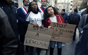 """Protestors hold placards reading """"Stop slavery"""" as they attend a demonstration against slavery in Libya outside the Lybian Embassy in Paris, Friday, Nov. 24, 2017. Interpol says 40 suspected human traffickers have been arrested and nearly 500 of their victims freed in a vast police operation in five African countries. (AP Photo/Thibault Camus)"""