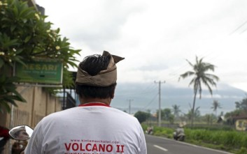 A man watches Mount Agung volcano which is covered by clouds in Karangasem, Bali, Indonesia, Thursday, Nov. 30, 2017. Authorities have told tens of thousands of people to leave an area extending 10 kilometers (6 miles) from the volcano as it belches volcanic materials into the air. Mount Agung's last major eruption in 1963 killed about 1,100 people. (AP Photo/Firdia Lisnawati)