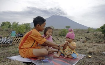Children sit with a backdrop of the Mount Agung volcano erupting as they wait for their parents work in a field in Karangasem, Bali, Indonesia, Wednesday, Nov. 29, 2017. The volcano with a deadly history on Indonesia's Bali, one of the world's most popular resort islands, has spewed ash 7,600 meters (4.7 miles) high and closed the island's international airport for a third day Wednesday. (AP Photo/Firdia Lisnawati)
