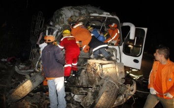 Firefighters and rescue workers try to free wounded people from the wreckage of a bus that crashed in Cerro Bravo, near Manizales, Colombia, early Saturday, Jan. 5, 2013. According to highway police authorities, 11 passengers died and 31 were wounded in the bus that was traveling to Bogota. (AP Photo/Maria Luisa Garcia)