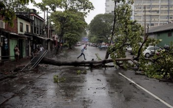 A Sri Lankan man runs for cover as it rains next to a fallen tree in Colombo, Sri Lanka, Thursday, Nov. 30, 2017. Sri Lanka's government says storms with heavy rain and winds across the country have left at least four people dead and several fishermen are among 23 people missing. (AP Photo/Eranga Jayawardena)