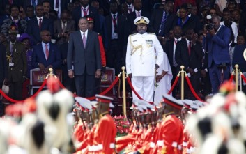 Kenyan President Uhuru Kenyatta and Army Chief of Staff, General Samson Mwathethe, right, watch as armed forces of the Republic of Kenya march, during Kenyatta's inauguration ceremony at Kasarani stadium in Nairobi, Kenya Tuesday, Nov. 28, 2017. Kenyan President Uhuru Kenyatta was sworn in on Tuesday, ending a months-long election drama that saw the first vote nullified by the country's top court and the second boycotted by the opposition. (AP Photo/Sayyid Abdul Azim)