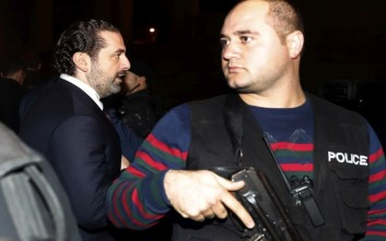 Lebanese Prime Minister Saad Hariri, left, escorted by his bodyguards as he walks to pray over his father's grave, upon his arrival to Beirut, Lebanon, Tuesday, Nov. 21, 2017. Hariri has returned to Beirut more than two weeks after announcing while in Saudi Arabia that he had resigned his post. (AP Photo/Hussein Malla)