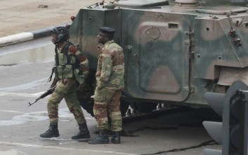 Armed soldiers stand by an armored vehicle on the road leading to President Robert Mugabe's office in Harare, Zimbabwe Wednesday, Nov. 15, 2017. Zimbabwe's army said Wednesday it has President Robert Mugabe and his wife in custody and is securing government offices and patrolling the capital's streets following a night of unrest that included a military takeover of the state broadcaster. (AP Photo/Tsvangirayi Mukwazhi)