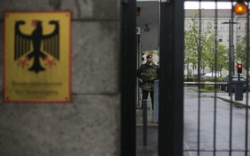 A guard stands at the entrance of the German Defense Ministry prior to a meeting between Defense Minister Ursula von der Leyen and about 100 top officers in Berlin, Thursday, May 4, 2017. The meeting is held to determine where mistakes were made in case of an army officer arrested last week on suspicion that he was part of a small group planning a far-right attack. (AP Photo/Markus Schreiber)