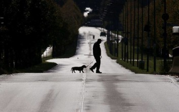 An elderly man and his Dachshund cross a long main road in the outskirts of Frankfurt, Germany, on a national holiday, Tuesday, Oct. 3, 2017. (AP Photo/Michael Probst)