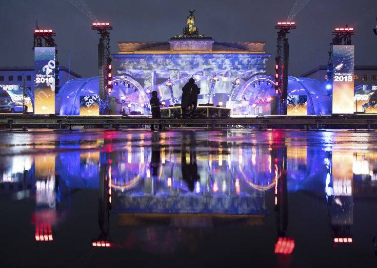 The illuminated Brandenburg Gate reflects in a puddle during a rehearsal prior to the New Year's Eve party of in Berlin, Germany, Saturday, Dec. 30, 2017. (Ralf Hirschberger/dpa via AP)