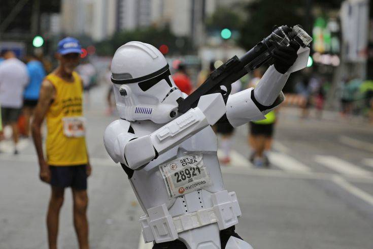 A runner dressed as a Star Wars storm trooper poses for a photo prior to the start of the Sao Silvestre race in Sao Paulo, Brazil, early Sunday, Dec. 31, 2017. The 15-kilometer race is held annually on New Year's Eve. (AP Photo/Nelson Antoine)