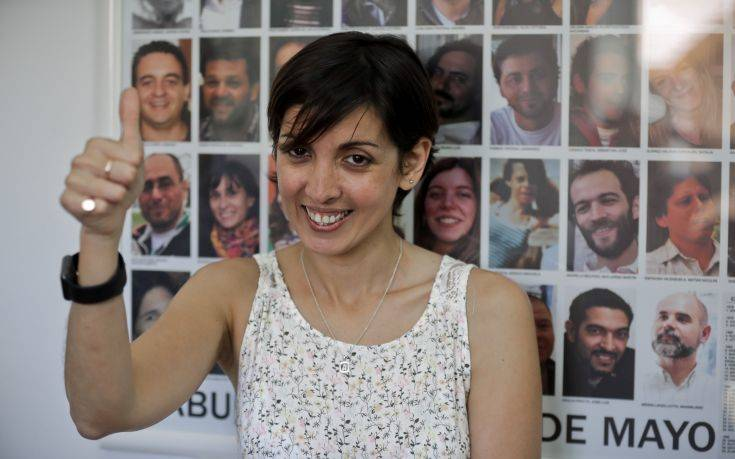 Adriana, daughter of two activists who were killed during the Argentine dictatorship in 1976, flashes a thumbs up in front of photos of people who also recovered their identities, in Buenos Aires, Argentina, Tuesday, Dec. 5, 2017. The human rights group Grandmothers of the Plaza de Mayo said Tuesday that DNA tests have determined the real identity of Adriana, the missing daughter of Violeta Graciela Ortolani and Edgardo Roberto Garnier, bringing the number of cases of recovered stolen children from the Argentine dictatorship to 126. (AP Photo/Victor R. Caivano)