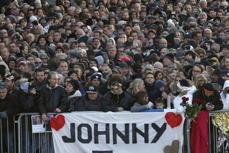 People wait outside the Madeleine church to attend French rock star Johnny Hallyday's funeral ceremony, in Paris, France, Saturday, Dec. 9, 2017. France is bidding farewell to its biggest rock star, honoring Johnny Hallyday with an exceptional funeral procession down the Champs-Elysees, a presidential speech and a motorcycle parade — all under intense security. (AP Photo/Thibault Camus)