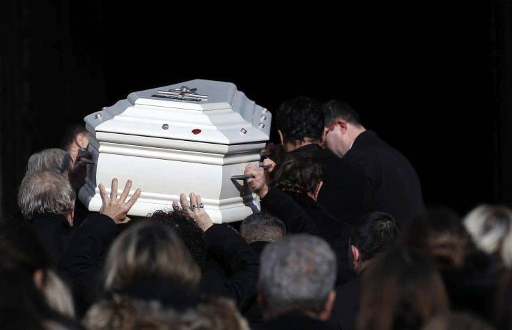 The coffin of French rock singer Johnny Hallyday is carried into La Madeleine church Saturday Dec. 9, 2017 in Paris. France is bidding farewell to its biggest rock star, honoring Johnny Hallyday with an exceptional funeral procession down the Champs-Elysees, a presidential speech and a parade of motorcyclists — all under intense security. (Yoan Vallat, Pool via AP)