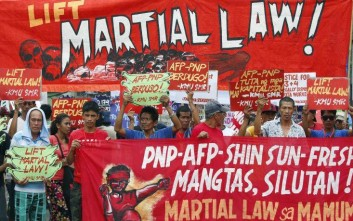 Protesters hold placards to protest the extension of martial law on Mindanao island in southern Philippines, Tuesday, July 18, 2017, in Manila, Philippines. Duterte asked for an extension till the end of the year on the marshall law he declared on May 23, 2017, following a bloody siege of southern Marawi city by Islamic State group-aligned militants, the most serious security crisis he has faced since assuming power in June last year. (AP Photo/Bullit Marquez)
