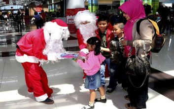 Indonesians dressed as Santa Claus hand out gifts to child travelers as part of Christmas celebrations at Soekarno-Hatta International Airport in Jakarta, Indonesia, Wednesday, Dec., 24, 2014. (AP Photo/Tatan Syuflana)