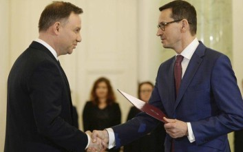 Polish President Andrzej Duda, left, designates Finance Minister Mateusz Morawiecki, right, for the prime minister's post, in Warsaw, Poland, Friday, Dec. 8, 2017. (AP Photo/Alik Keplicz)
