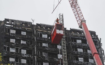 Workers put up scaffolding at the Grenfell Tower in London, Friday, Oct. 13, 2017. Work has begun to cover the ruin of Grenfell Tower, nearly four months after a fire inflicted the most costly tragedy in recent British history. The Royal Borough of Kensington and Chelsea (RBKC) said the work was expected to be completed in the first few months of 2018. Around 80 people died and hundreds were left homeless in the disaster, which triggered the launch of a public inquiry and an enormous criminal investigation. (AP Photo/Frank Augstein)