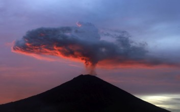 In this Nov. 30, 2017, file photo, clouds of ash from Mount Agung volcano are lit with warm sunset light in Karangasem, Bali, Indonesia. Authorities have told tens of thousands of people to leave an area extending 10 kilometers (6 miles) from the volcano as it belches volcanic materials into the air. Mount Agung's last major eruption in 1963 killed about 1,100 people. (AP Photo/Firdia Lisnawati, File)