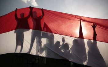 Men are silhouetted against a large representation of the Yemeni flag as they attend a ceremony to mark the anniversary of North Yemen's Sept. 26, 1962 revolution in Sanaa, Yemen, Monday, Sept. 26, 2016. The ceremony marked the 54th anniversary of the revolution that overthrew the Imamate and moved into a new period in northern Yemen that turned Yemen into a republic. (AP Photo/Hani Mohammed)