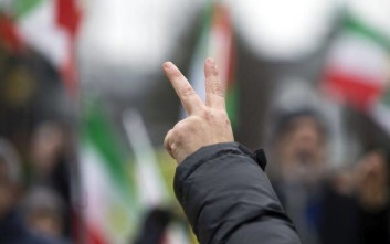 Supporters chant slogans and wave flags of the National Council of Resistance of Iran as they demonstrate outside EU headquarters in Brussels on Wednesday, Jan. 10, 2018. Protestors demonstrated against a meeting, between the EU and Iran, which will take place in Brussels on Thursday, Jan. 11, 2018. (AP Photo/Virginia Mayo)