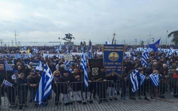 Κρατούν ελληνικές σημαίες και χορεύουν παραδοσιακούς χορούς