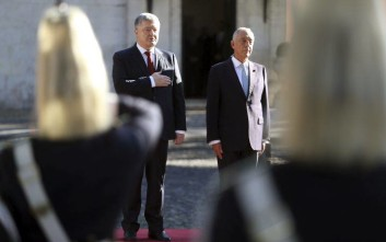 Ukraine's President Petro Poroshenko, left, and Portuguese President Marcelo Rebelo de Sousa listen to the national anthems during a welcome ceremony at the Belem presidential palace in Lisbon Monday, Dec. 18, 2017. (AP Photo/Armando Franca)