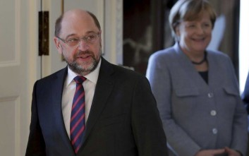 Martin Schulz, Chairman of the German Social Democratic Party (SPD), left, and German Chancellor Angela Merkel queue up during a New Year's reception of German President Frank-Walter Steinmeier at the Bellevue palace in Berlin, Germany, Tuesday, Jan. 9, 2018. (AP Photo/Michael Sohn)