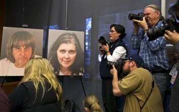 Members of the media photograph police photos of fifty-seven-year-old David Allen Turpin, left, and 49-year-old Louise Anna Turpin, center, during a news conference with Riverside County District Attorney Mike Hestrin in Riverside, Calif., Thursday, Jan. 18, 2018. Hestrin says all 13 victims were severely malnourished and as a result some have cognitive impairment and a lack of basic knowledge of life. He says a 29-year-old female victim weight 82 pounds. (AP Photo/Damian Dovarganes)