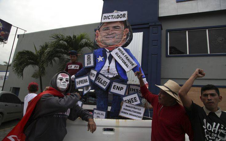 Opposition supporters rally alongside a cardboard figure of President Juan Orlando Hernandez, labelled with Spanish phrases including