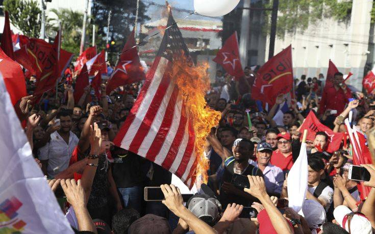 Opposition supporters burn a flag of the United States, which recognized disputed election results handing victory in November's presidential election to incumbent Juan Orlando Hernandez, during a march and rally led by opposition leader Salvador Nasralla in San Pedro Sula, Honduras, Saturday, Jan. 6, 2018. Following an election marred by irregularities, Hernandez was declared the victor and will be inaugurated on Jan. 27. Nasralla reaffirmed his claim on the presidency and said he would not stop calling for protests and civil disobedience until Hernandez agrees to step down. (AP Photo/Fernando Antonio)