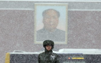 A Chinese paramilitary policeman stands on duty as heavy snow falls near a portrait of late Chinese leader Mao Zedong on Tiananmen Gate in Beijing, China, Sunday, Nov. 22, 2015. China's meteorological authority forecasted heavy snow and snowstorm in northern China over the weekend. (AP Photo/Ng Han Guan)