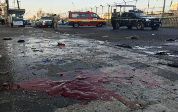 Iraqi security forces gather near blood stains at the scene of a double suicide bombing in central Baghdad, Iraq, Monday, Jan. 15, 2018. Interior Ministry spokesman says a double suicide bombing in central Baghdad has killed and wounded civilians. (AP Photo/Ali Abdul Hassan)