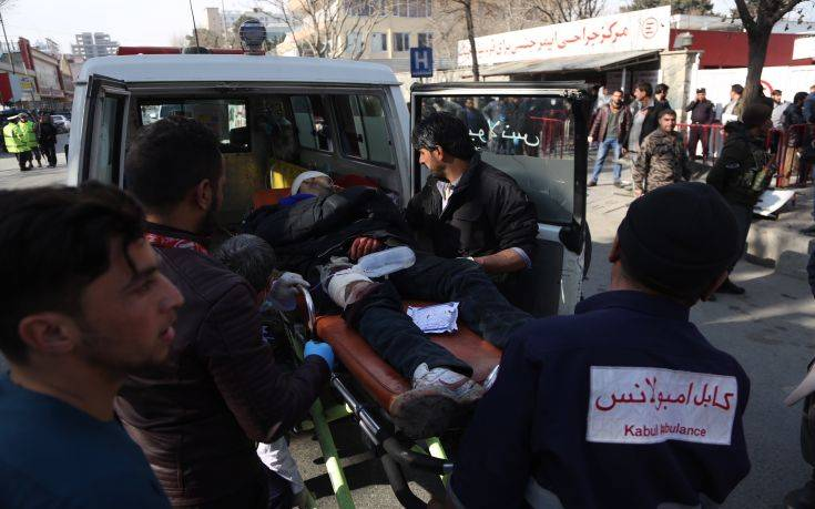 A wounded man is assisted to a hospital following a deadly suicide attack in the center of Kabul, Afghanistan, Saturday, Jan. 27, 2018. Afghan Public Health Ministry says dozens have been killed and over 100 wounded in suicide car bomb attack in capital Kabul. (AP Photo/Massoud Hossaini)
