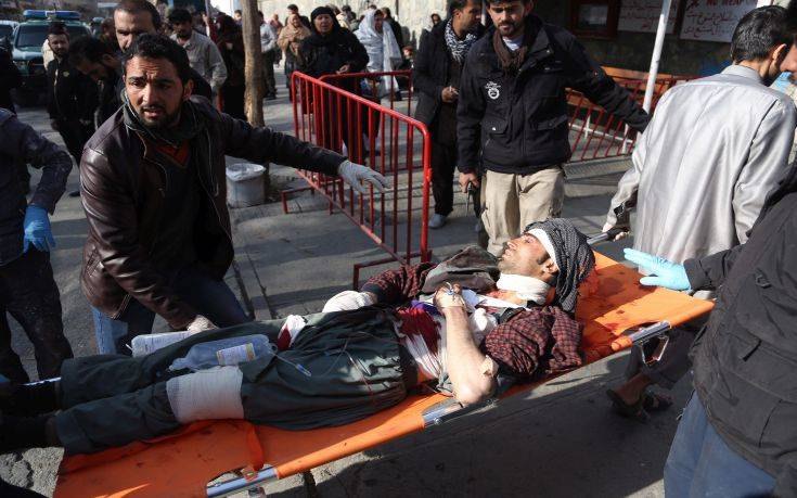 People help carry an injured man to the hospital following a suicide attack in Kabul, Afghanistan, Saturday Jan. 27, 2017. The Public Health Ministry says over a dozen were killed, and over 100 wounded ina suicide car bombing in downtown Kabul. (AP Photo/ Rahmat Gul)
