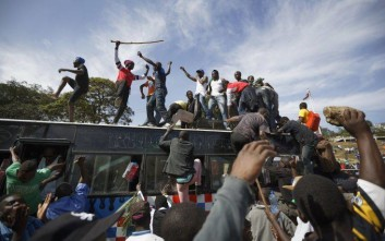 """Supporters of opposition leader Raila Odinga arrive by bus, as they gather in advance of a mock """"swearing-in"""" ceremony of Odinga at Uhuru Park in downtown Nairobi, Kenya Tuesday, Jan. 30, 2018. Odinga is due Tuesday to hold a so-called """"inauguration"""" of himself in protest of President Uhuru Kenyatta's new term following the divisive 2017 election. (AP Photo/Ben Curtis)"""