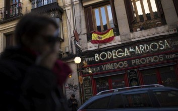 A woman walks past a building with a Spanish flag hanging in a balcony in Madrid, Wednesday, Jan. 17, 2018. A new Catalan parliament is meeting following a botched secession attempt last year and amid looming questions about the role that fugitive and jailed politicians will play in the chamber's separatist majority. (AP Photo/Francisco Seco)