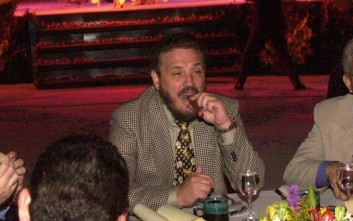 Fidel Castro's eldest son, Fidelito, center, puffs away on a cigar during the opening of the international cigar festival Monday Feb. 25, 2002. Over the next five days, about 600 cigar enthusiasts from 47 different countries will try out new brands, visit tobacco plantations, and go to elegant receptions and a dlrs 400-a-head dinner traditionally attended by President Fidel Castro. (AP Photo/Cristobal Herrera)