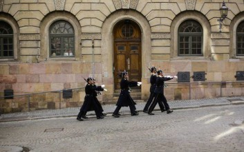 Honor guards march through the old town in direction to the King's palace in Stockholm, Sweden, Sunday, April 9, 2017. (AP Photo/Markus Schreiber)