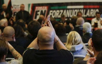 A man applauds as Italy's neo-fascist Forza Nuova leader Roberto Fiore speaks during a press conference, in Como, Italy, Saturday, Dec. 9, 2017. Italy's governing Democrats have led a rally to warn about fascism's making a comeback in the nation, which had suffered under fascist dictator Benito Mussolini. Several thousand people turned out in Como, northern Italy, where recently right-wing extremists interrupted an NGO meeting about migrants' housing. Earlier this week, a neo-fascist party attacked the Rome office of a liberal newspaper. (AP Photo/Luca Bruno)