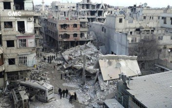 In this photo released on Thursday Feb. 22, 2018 which provided by the Syrian anti-government activist group Ghouta Media Center, which has been authenticated based on its contents and other AP reporting, shows Syrians gather between destroyed buildings which attacked during airstrikes and shelling by Syrian government forces, in Ghouta, a suburb of Damascus, Syria. A new wave of deadly Syrian government bombardment in the opposition-held eastern suburbs of the capital Damascus on Thursday killed 13 people as world leaders and aid groups called for an end to the carnage that has left hundreds of people dead in recent days.(Ghouta Media Center via AP)