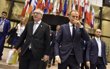 European Commission President Jean-Claude Juncker, center left, and European Council President Donald Tusk, center right, walk together to a media conference at the end of an EU summit at the Europa building in Brussels on Friday, Feb. 23, 2018. European Union leaders met without Britain Friday looking to plug a major budget hole after Brexit and endorse a plan to streamline the European Parliament by sharing out the country's seats. (AP Photo/Geert Vanden Wijngaert)