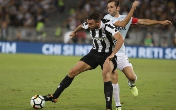 Juventus' Andrea Barzagli, left, and Lazio's Send Lulic vie for the ball during the Italian Super Cup final match between Lazio and Juventus at Rome's Olympic stadium, Sunday, Aug. 13, 2017. (AP Photo/Gregorio Borgia)
