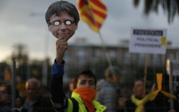 A pro independence demonstrator holds up a Carles Puigdemont mask during a protest of the detention of deposed leader of Catalonia's pro-independence party Carles Puigdemont in Barcelona, Spain, Sunday, March 25, 2018. Puigdemont was arrested Sunday by German police on an international warrant as he tried to enter the country from Denmark. (AP Photo/Manu Fernandez)