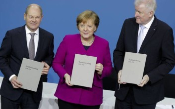 From left, Olaf Scholz, acting chairman of the German Social Democratic Party (SPD), German Chancellor and chairwomen of the German Christian Democratic Union (CDU), Angela Merkel, and the chairman of the German Christian Social Union (CSU), Horst Seehofer, pose with the coalition agreement during a signing ceremony in Berlin, Germany, Monday, March 12, 2018. (AP Photo/Markus Schreiber)