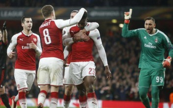 Arsenal's Danny Welbeck celebrates with his teammate Aaron Ramsey, left, after scoring his side opening goal on a penalty, as AC Milan goalkeeper Gianluigi Donnarumma gestures, during the Europa League round of 16 second leg soccer match between Arsenal and AC Milan at the Emirates stadium in London, Thursday, March, 15, 2018. (AP Photo/Alastair Grant)