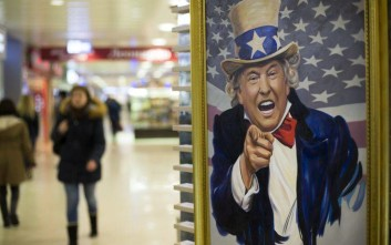 People walk past a caricature picture of U.S. President Donald Trump on sale in a shopping mall in Moscow, Russia, Wednesday, March 22, 2017. President Donald Trump's former campaign chairman, Paul Manafort, secretly worked for a Russian billionaire to advance the interests of Russian President Vladimir Putin a decade ago and proposed an ambitious political strategy to undermine anti-Russian opposition across former Soviet republics, The Associated Press has learned. (AP Photo/Alexander Zemlianichenko)