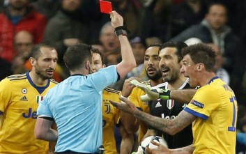 Referee Michael Oliver shows a red car to Juventus goalkeeper Gianluigi Buffon during a Champions League quarter final second leg soccer match between Real Madrid and Juventus at the Santiago Bernabeu stadium in Madrid, Wednesday, April 11, 2018. (AP Photo/Francisco Seco)