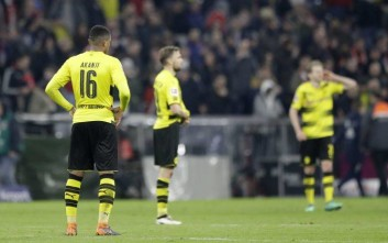 Dortmund's Manuel Akanji and his team mates stand on the pitch after the German Bundesliga soccer match between FC Bayern Munich and Borussia Dortmund in Munich, Germany, Saturday, March 31, 2018. (AP Photo/Matthias Schrader)