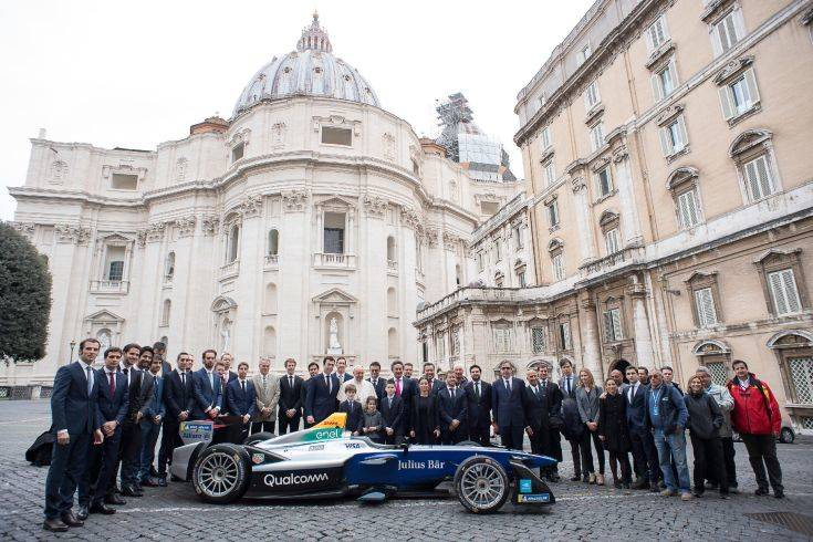 Pope Francis poses with the Formula E electric official car, at the Vatican, Wednesday, April 11, 2018. A Formula E race will be held in Rome EUR district, Saturday, April 14. (Vatican Media via AP)